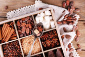 Wooden box with set of coffee and cocoa beans, sugar cubes, dark chocolate, cinnamon and anise, close-up, on wooden background — Foto de Stock