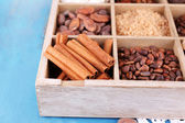 Wooden box with set of coffee and cocoa beans, sugar cubes, dark chocolate, cinnamon and anise on wooden background — Stock Photo