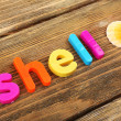 Shell word formed with colorful letters on wooden background — Stock Photo #61007039