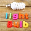 Light bulb word formed with colorful letters on wooden background — Stock Photo #61007051