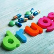 Drugs word formed with colorful letters on wooden background — Stock Photo #61007187