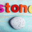 Stone word formed with colorful letters on wooden background — Stock Photo #61007197