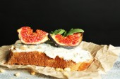 Tasty sandwich with sweet figs and cottage cheese on wooden table, on dark background — Stock Photo