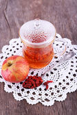 Goji berries drink in glass cup, ripe apple and raisins in metal spoon on lace napkin on wooden background — Stock Photo