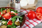 Eggplant salad with tomatoes, arugula and feta cheese, on napkin, on color wooden background — Stock Photo