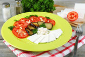 Eggplant salad with tomatoes and feta cheese, on napkin, on wooden background — Foto de Stock