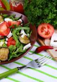 Eggplant salad with tomatoes, arugula and feta cheese, on napkin, on color wooden background — Foto de Stock