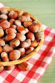 Hazelnuts on wicker mat on wooden background — Stock Photo