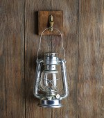 Lantern hanging on hook on wooden wall — Stock Photo