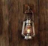 Lantern hanging on hook on wooden wall — Stock Photo