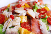 Appetizing fish salad with vegetables on plate close-up background — Stock Photo