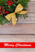 Beautiful Christmas border from fir and mistletoe on wooden background — Stock Photo