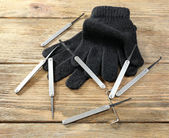 Lock picks with gloves on wooden table — Stock Photo