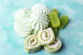 Mint color meringues and mint jelly candies on color background — Stock Photo