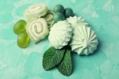 Mint color meringues and candies on color background — Stock Photo