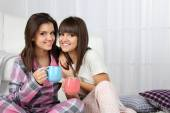 Beautiful girls twins in pajamas drinking tea at home — Stockfoto