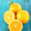Ripe tangerines and oranges with leaves on wooden background — Stock Photo #61044695