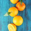 Ripe tangerines and oranges with leaves on wooden background — Stock Photo #61044735
