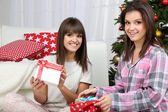 Beautiful girls twins in pajamas near Christmas tree at home — Stock Photo