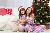 Beautiful girls twins in pajamas near Christmas tree at home — Stock Photo