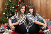 Beautiful girls twins near Christmas tree at home — Stock Photo
