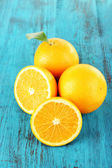 Ripe tangerines and oranges with leaves on wooden background — Stock Photo
