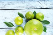 Ripe sweetie and limes on wooden background — ストック写真