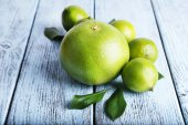 Ripe sweetie and limes on wooden background — Stock fotografie