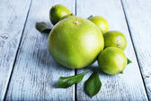 Ripe sweetie and limes on wooden background — Photo