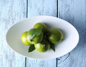 Fresh juicy limes on plate — Stockfoto