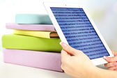 Female hand holding PC tablet near books, close-up. Modern  education concept — Stock Photo
