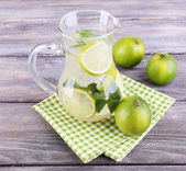 Lemonade in pitcher on wooden background — Stock Photo