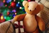 Teddy bear and gift box in rocking chair on Christmas tree background — Stock Photo