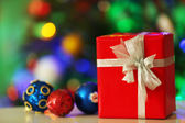 Gift box and decorations on Christmas tree lights background — Stock Photo