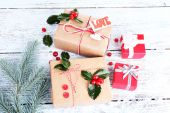 Beautiful Cristmas gifts with European Holly (Ilex aquifolium) on wooden background — Stock Photo