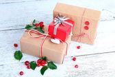Beautiful Cristmas gifts with European Holly (Ilex aquifolium) on wooden background — Stock Photo