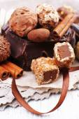 Pile of chunk of chocolate and truffles with cinnamon stick on crumbled paper, grey material and wooden background — Stok fotoğraf