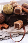 Pile of chunk of chocolate and truffles with cinnamon stick on crumbled paper, grey material and wooden background — Stock Photo