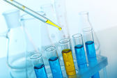 Pipette adding yellow fluid — Stock Photo