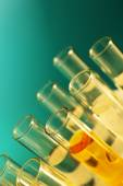 Test-tubes with colorless liquid and yellow one, on the blue background — Stock Photo