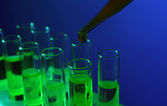 Pipette adding liquid to the one of test-tubes on dark background — Stock Photo