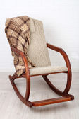 Rocking chair covered with plaid on wooden floor near the brick wall background — ストック写真