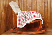 Rocking chair covered with plaid on wooden wall background — Stock fotografie