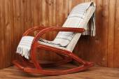 Rocking chair covered with plaid on wooden wall background — Fotografia Stock