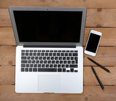 Pens and smart phone with notebook — Stock Photo
