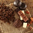 Pile of coffee beans with chocolate, nuts and cinnamon on burlap cloth on wicker mat — Stock Photo #61082115