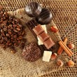 Pile of coffee beans with chocolate, nuts and cinnamon on burlap cloth on wicker mat — Stock Photo #61082155
