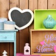 Beautiful colorful shelves with different home related objects on wooden wall background — Stock Photo #61088803