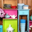 Beautiful colorful shelves with different home related objects on wooden wall background — Stock Photo #61088829