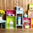 Beautiful colorful shelves with different home related objects on wooden wall background — Stock Photo #61088863